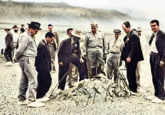 Robert Oppenheimer (light hat) and General Leslie Groves (right of Oppenheimer) at the ground zero point of the Trinity Test after the bombing of Hiroshima and Nagasaki (some time after the Trinity Test) at tower foundation reinforced concrete remains