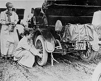 Alice Huyler Ramsey (1887-1983) in 1909. Asphalt roads were a rarity and repairs frequent during the pioneer cross-country drive of Alice Huyler Ramsey in 1909. Shown here changing a tire on her green Maxwell