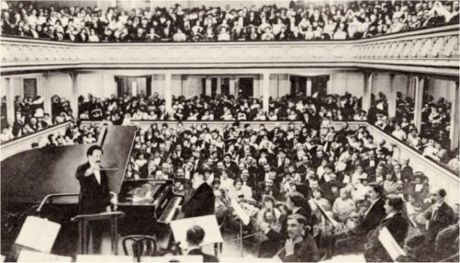 Saint-Saëns at the piano for his planned farewell concert in 1913, conducted by Pierre Monteux