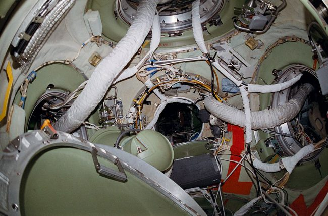 A view of the interior of the docking node of the Russian space station Mir's core module, showing the hatches leading to the station's various modules and the cables and hoses trailing through them.