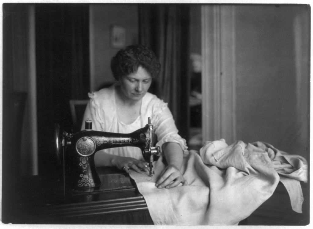 Woman working with singer machine (ca. 1914) Image Source: Library of Congress