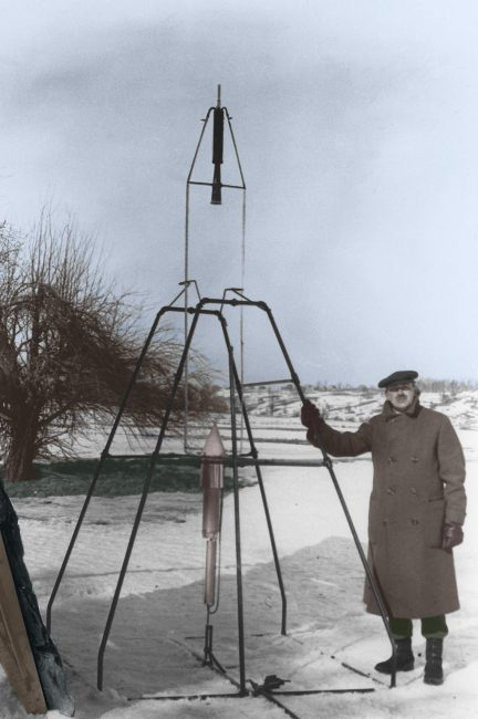Robert Goddard holds the launching frame of the first liquid-fueled rocket.