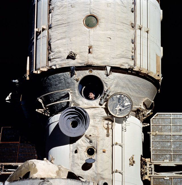 Polyakov observes rendezvous operations with the Space Shuttle Discovery on its STS-63 mission through a window on the Mir Core Module in February 1995.