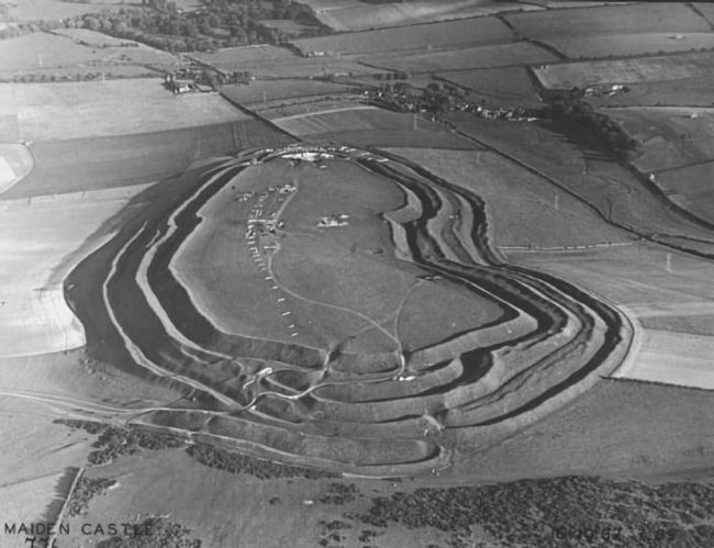 An aerial view of Maiden Castle in Dorset from the west. Wheeler led excavations at the Iron Age hill fort of Maiden Castle. Photograph by Major George Allen, October 1937
