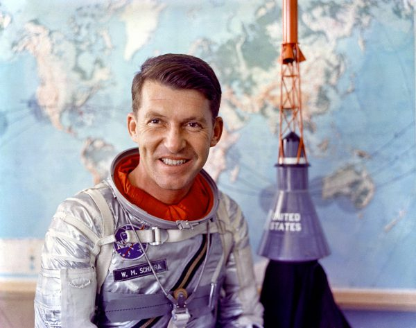 Walter M. Schirra Jr. in Mercury pressure suit with model of Mercury capsule behind him