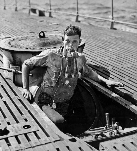 "USS V-5 (SC 1) crewman A. L. Rosenkotter exits the submarine's escape hatch wearing the ""Momsen Lung"" emergency escape breathing device during the submarine's sea trials in July, 1930"
