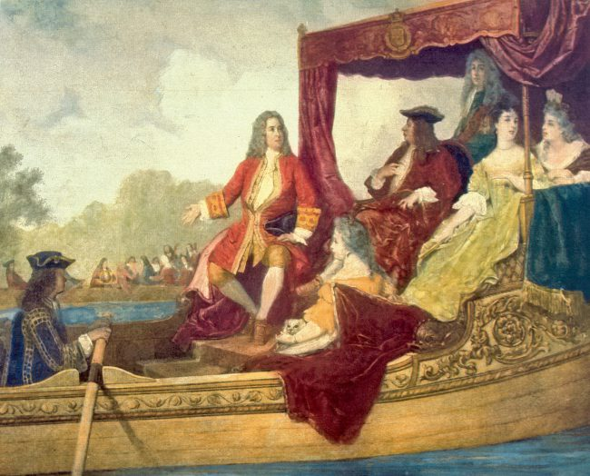 Painting of George Frideric Handel (left, with right arm extended) with King George I of Great Britain, traveling by barge on the Thames River while musicians play in the background. The painting is an artist's rendering of the first performance of Handel's Water Music in 1717.