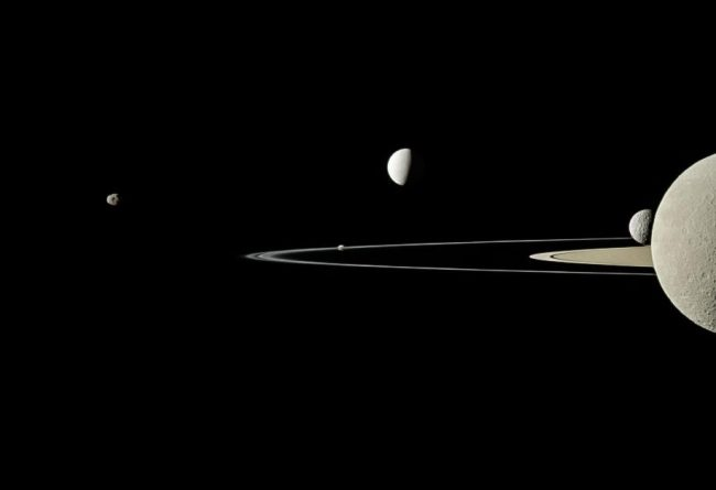 Five moons in another Cassini image: Rhea bisected in the far-right foreground, Mimas behind it, bright Enceladus above and beyond the rings, Pandora eclipsed by the F Ring, and Janus off to the left.