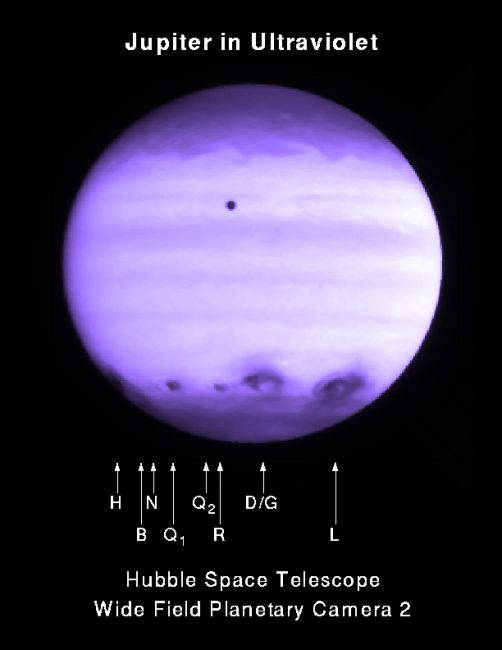 Dark spots in the atmosphere of the planet Jupiter after the impact of comet Shoemaker-Levy 9 (the point above is the Jupiter moon Io), ultraviolet image of July 21, 1994 (HST, NASA).