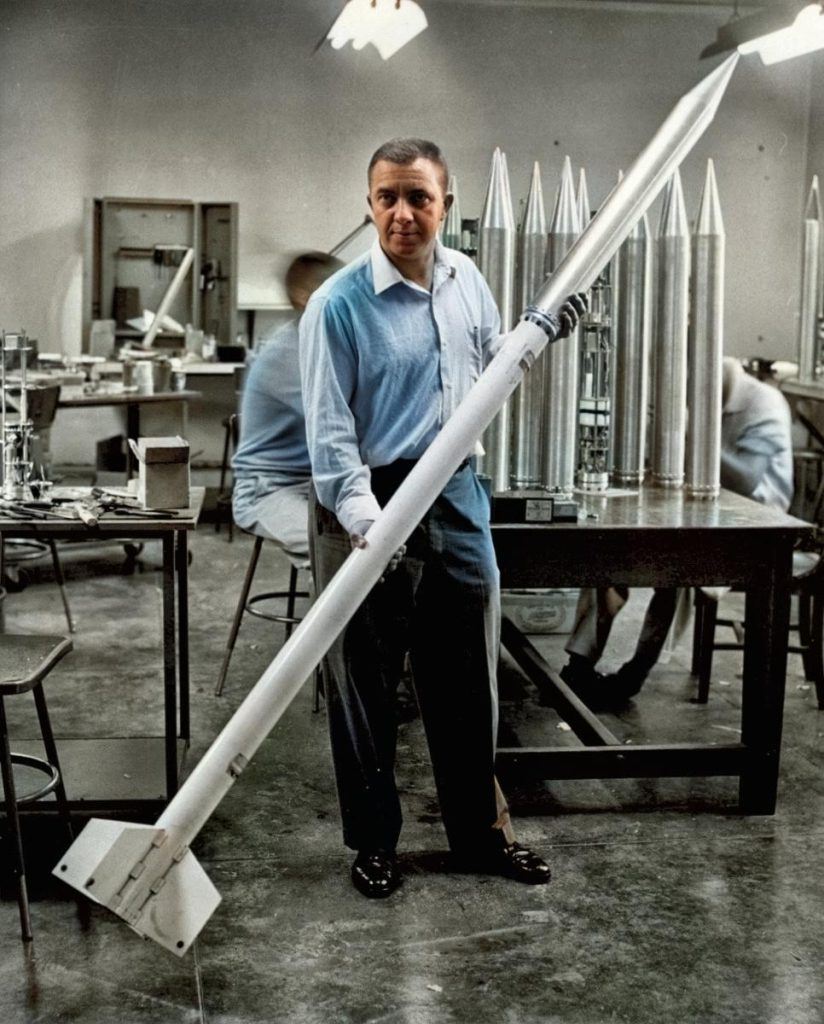 James Van Allen of the University of Iowa poses in workshop with a rocket and scientific instrument package