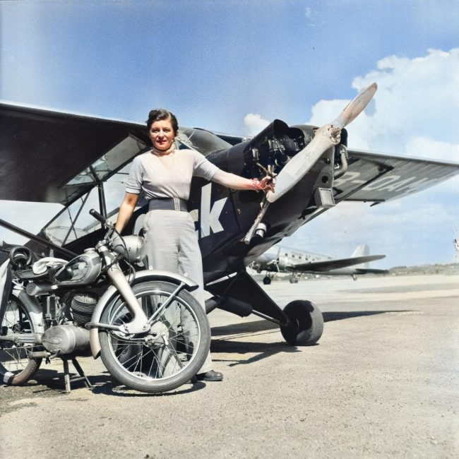 Woman in Helsinki 1952 Summer Olympics. Plane in the background is Elly Beinhorn's Piper J-3C-65 Cub with designation HB-OAM and description of the photo says that it is most likely herself.