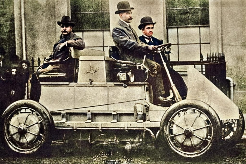 Lohner Porsche Race Car, 1902. At the wheel of the car: E. W. Hart from Luton, England. Next to it: Ferdinand Porsche. The vehicle has four wheel hub motors with an output of 1500 W each. The electric current is stored in accumulators with a total mass of 1800 kg.