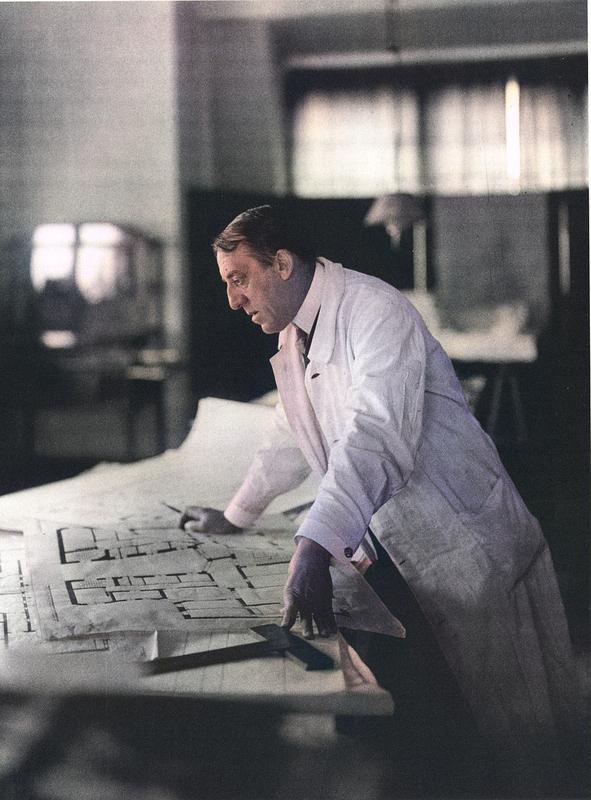 Henry van de Velde in the studio above the floor plan of the new pastorate building in Riga, around 1911.jpg