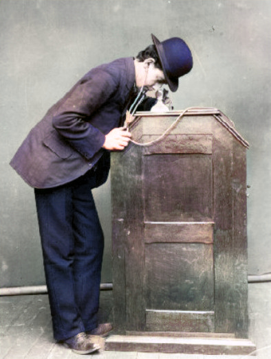 The 1895 version of the Kinetoscope with earphones that lead to the cylinder phonograph within the cabinet