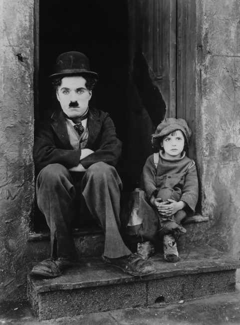 Publicity photo from Charlie Chaplin's 1921 film The Kid, featuring Charlie Chaplin (left) and Jackie Coogan (right).